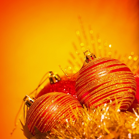 Image of red Christmas bubbles border, festive decorations isolated on orange background, golden holiday ornaments, beautiful greeting card, New Year still life, traditional xmas decor  photo