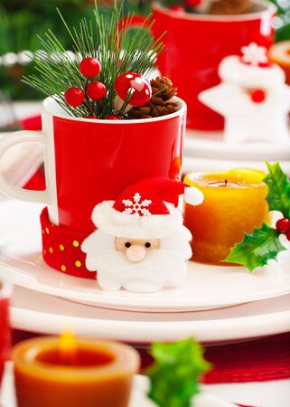 christmas eve: Photo of New Year eve table setting, closeup Christmas still life, Christmastime decoration for dinner, red and white festive utensil with candle and Santa Claus decoration, wintertime holiday
