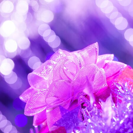 Picture of pink ribbon bow on purple glowing background  photo