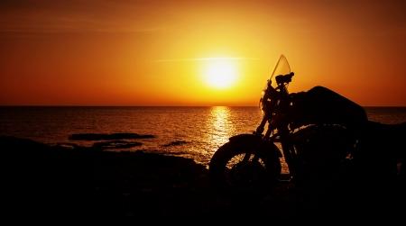 motor race: Afbeelding van luxe motorfiets op het strand in de nacht, silhouet van de motor op zonsondergang