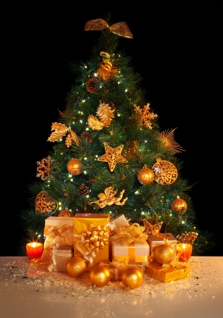 Image of gifts under beautiful Christmas tree isolated on black background, green fir tree decorated with golden balls photo