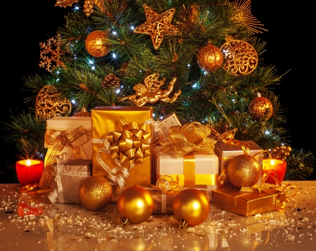 adorned: Picture of many golden presents boxes under luxury Christmas tree, beautiful adorned New Year spruce