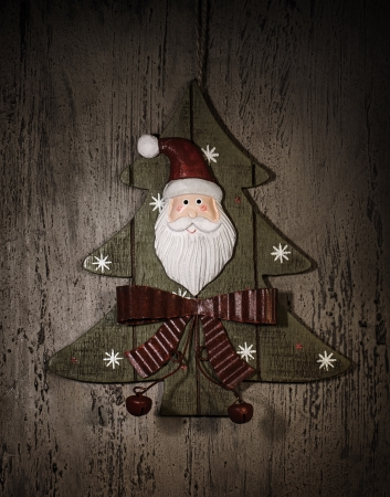 Grunge photo of Christmastime decoration, decorative wooden Christmas tree with Santa Claus ornament photo