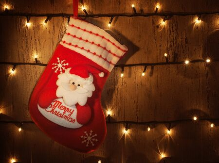 Picture of traditional red Christmas sock hanging on decorated door at home photo