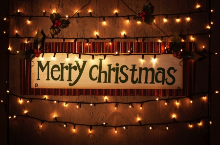 christmas illuminations: Picture of Merry Christmas banner on brown grunge door at home