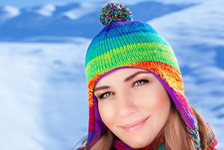 A pretty woman having fun on snowy mountains, closeup portrait of cute teenager wearing knitted colorful hat with bubo, wintertime fashion style, warm winter fashionable clothes  photo