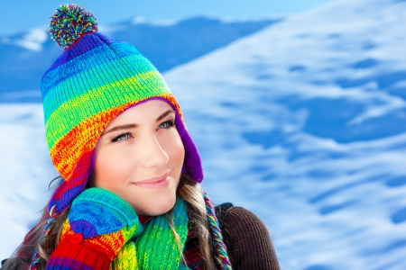 Picture of cute girl wearing colorful knitted hat with scarf and gloves on winter background, pretty teenager having fun on mountains covered snow, wintertime fashionable clothes, Christmas time  photo