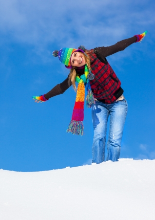 winter vacation: Image of pretty playful female having fun in winter park, cute woman standing with raised up hands on the top of snowy mountain, colorful hat and scarf, wintertime holidays, freedom concept