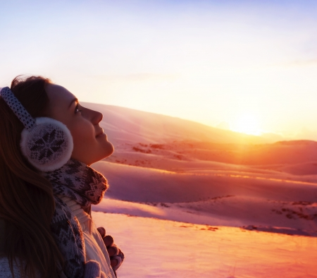 winter woman: A pretty woman walking in snowy mountains, side view of cute girl looking up, closeup portrait of female wearing warm winter earmuff, red sunset, wintertime sports, trekking and hiking concept