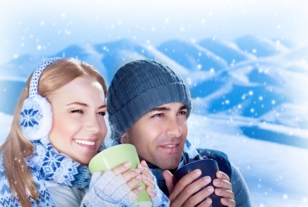 girl drinking: Picture of happy couple drink hot chokolate outdoors, beautiful woman with handsome man enjoying view of mountains covered white snow and holding cups of tea in hands, loving family, Christmas time Stock Photo
