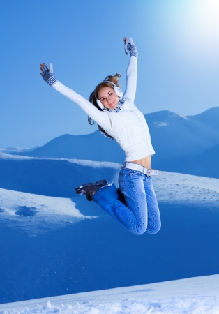 wintertime: A pretty girl jumping with raised up hands on snowy mountains, cute female playing on high mountain covered beautiful white snow, active lifestyle, happy wintertime holidays, winter concept