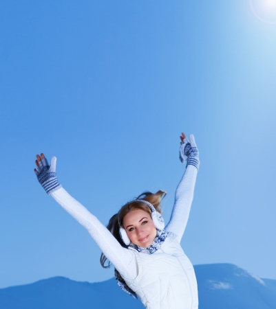 Image of pretty female with raised hands outdoors in winter, cute teenager girl jumping on the mountain, happines and freedom concept, Christmas holiday, wintertime vacation, New Year photo