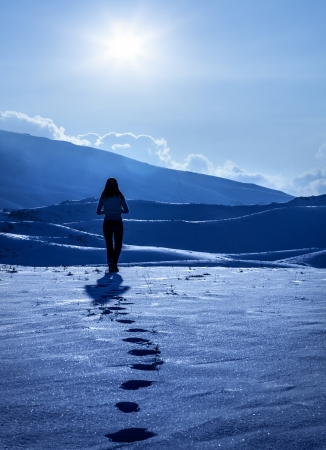 Image of lonely woman silhouette at winter mountains, footprints on the snow, enjoying wintertime nature view,one girl walking away on snowy path outdoor, winter cold weather, solitude concept photo