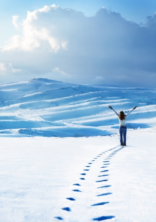 adult footprint: Happy woman jumping at winter mountains, active female enjoying nature, girl playing in the snow, teen having fun outdoor, healthy lifestyle and wintertime holidays vacation concept