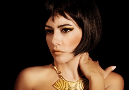 A gorgeous woman with Cleopatras makeup, closeup portrait of beautiful female with stylish haircut isolated on black background, young lady wearing fashionable golden necklace, beauty salon photo