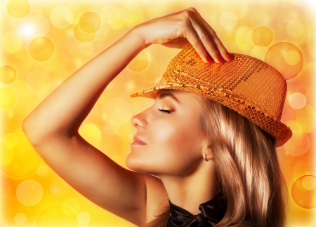 night life: A beautiful blond woman wearing stylish golden shiny hat, rear view of gorgeous female with closed eyes isolated on yellow blur background, disco club, night life, New Year party, Christmas eve