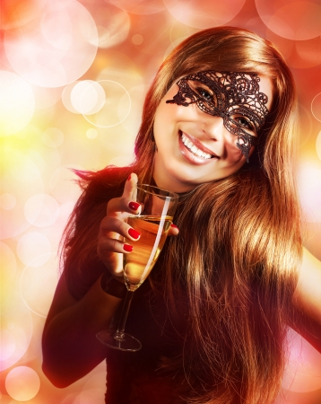 new years eve party: A sexy young lady wearing black lace mask isolated on blur background, luxury woman holding glass of champagne in hand, New Year carnival, Christmas masquerade, dance club, mystery night party Stock Photo