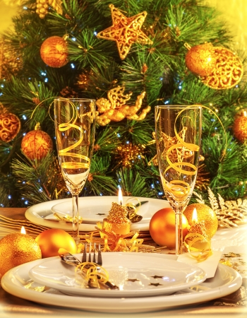 Christmas eve dinner in restaurant, Christmastime table setting over decorated fir tree background, white plates served with knife and fork, two glass for champagne decorated with golden ribbon, party photo