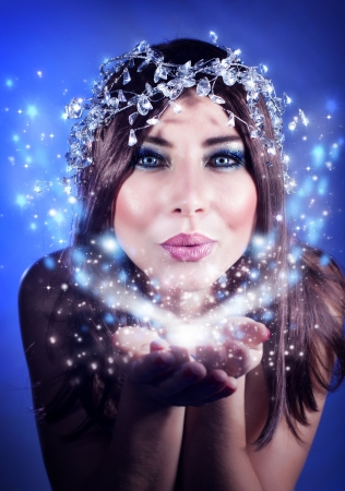 Photo of beautiful Christmas fairy blowing snow, woman holding snowflake, stunning female isolated on blue background, winter holiday magic light in hands, happy girl kiss, fashion, party makeup
