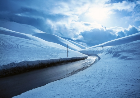 Picture of beautiful snowy highway, black clean asphalt road in mountains covered white snow, wintertime weather, blue cloudy sky, cold frosty day, Christmas vacation, landscape of driveway  photo