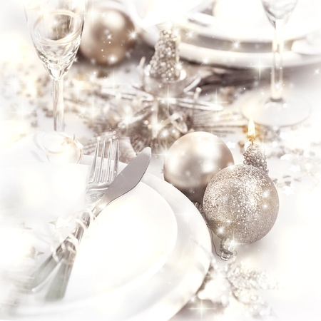 Picture of Christmastime table setting, white festive plate with knife and fork, shiny silver decoration, candle light, home interior, beautiful holiday dinnerware, romantic New Year dinner photo
