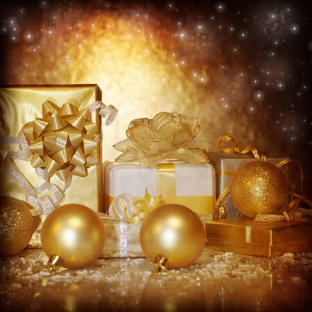 Image of traditional New Year gifts, Christmas present box wrapping in shiny golden festive paper, Christmastime still life isolated on dark glowing background, Xmas eve, holiday surprise photo