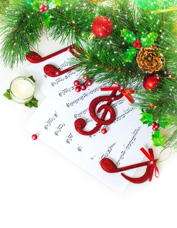 Image of red festive treble clef on the notes paper, Christmastime song, green fir tree decoration, traditional xmas carol, music sound, New Year greeting card, Christmas eve celebration photo