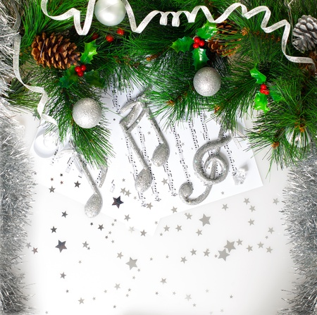 Picture of Xmas musical symbol, decorated green Christmas tree branch, shiny silver treble clef on note page, festive balls and cone hanging on fir tree, traditional Christmastime carol melody photo
