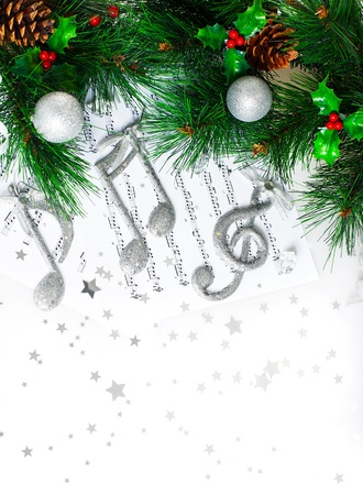 christmas music:  Christmas tree border, silver treble clef, festive melody on the notes page, musical sound, traditional Christmastime song, green pine tree branch decorated with cones, red berry and baubles