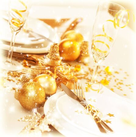 Picture of luxury festive table setting, beautiful white utensil decorated with golden balls and candles, elegant plate served with cutlery, Christmas home interior, New Year dinner photo