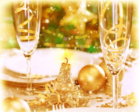 Photo of romantic holiday dinner, traditional adorned Christmas tree, two glasses for champagne, luxury white utensil decorated with golden baubles and candles, restaurant table setting photo