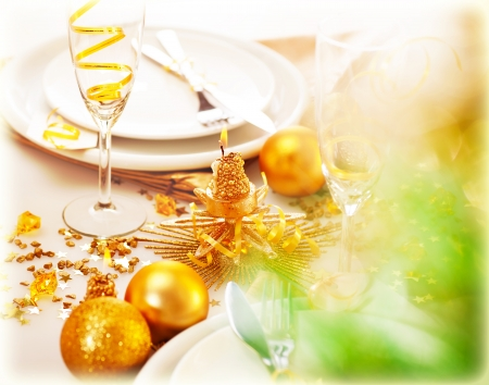 Picture of New Year table decorations, luxury festive table setting, romantic holiday dinner, white utensil adorned with golden shiny baubles, glasses for traditional Christmastime drink, champagne photo