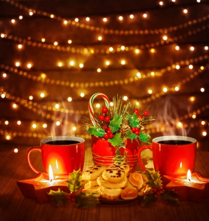 Photo of beautiful Christmas still life, red tea cups with tasty homemade cookies and candles on the wooden table on shiny brown background, electrical garland glowing on the wall, candy cane