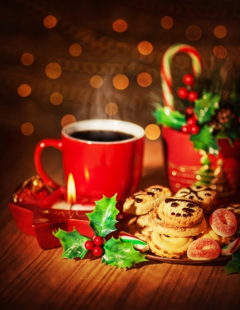 Picture of Christmas sweets still life, red mug with hot chocolate, branch of red berry, homemade gingerbread and tasty candy cane, sweet cookies, brown blur background, New Year dessert  photo