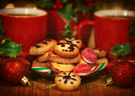 christmas tea: Image of Christmas dessert, festive sweet food still life, two coffee cups served with homemade cookies and decorated with red shiny balls, tasty candy cane and gingerbread, New Year table setting Stock Photo