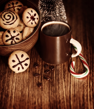 Picture of traditional Christmas sweets with cup of hot chocolate on wooden table, New Year dessert, roasted brown coffee bean, candy cane, little decorative festive pine tree, homemade cookies photo