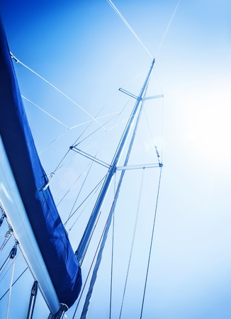 Sailboat in action, big white sail raised over blue clear sky, luxury leisure, summertime activities and extreme sport, boat parts with sun rays, sailing trip vacation, freedom concept photo