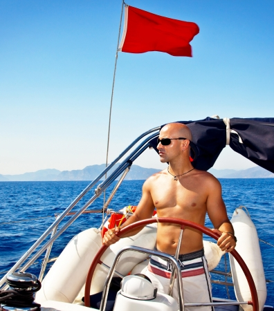 Photo of handsome muscular man at the helm of ship photo