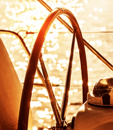 helm: Image of sailboat helm on sunset, steering wheel of yacht, rudder of vessel on sunrise, sea transportation, water transport, active lifestyle, summer vacation, ocean cruise concept  Stock Photo
