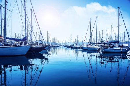 Picture of row of luxury sailboats reflected in water, yacht port on the bay, water transport, ocean transportation, beautiful vessel in the harbor, summer vacation, active lifestyle, holiday concept  Imagens