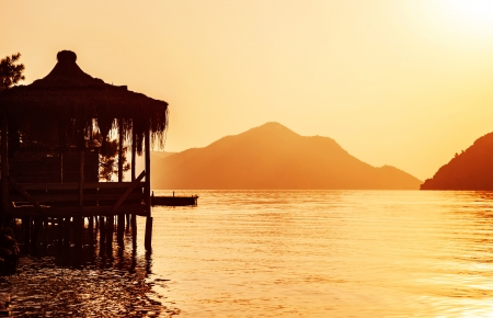 Image of Asian coastal luxury resort, beautiful little hut on the water, orange sunset, paradise beach, cute bungalow on sea shore, tropical travel, mountain landscape, vacation and holiday concept photo