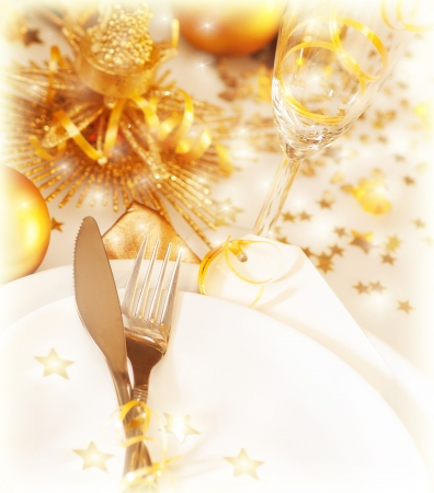 Photo of Christmastime table setting with golden festive decorations, luxury white plate served with silver cutlery and wine glass, Christmas holiday greeting postcard, New Year romantic dinner