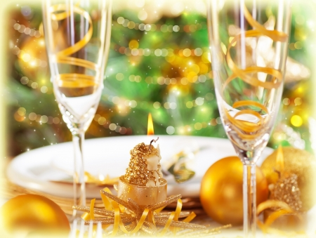 Picture of romantic holiday dinner in restaurant, Christmastime table setting with golden festive decorations, luxury white plate served with glass for champagne, beautiful adorned Christmas tree photo