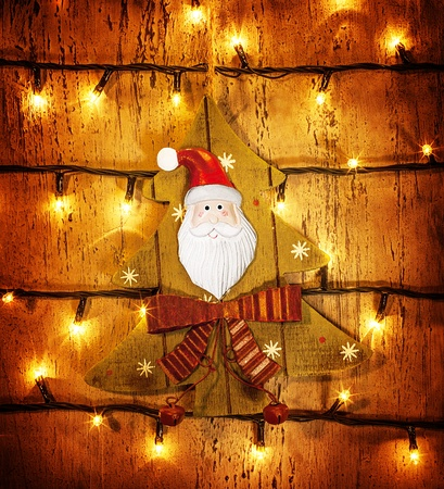 Picture of beautiful Christmastime ornament, little decorative Christmas tree hanging on wooden door adorned xmas lights, grunge glowing background, festive electrical garland, Santa Claus decor photo