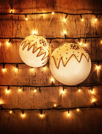 Image of two white New Year baubles hanging on wooden door, brown grungy wall decorated with Christmastime lights, cozy home festive decor, xmas ornament, Christmas holiday greeting postcard  photo