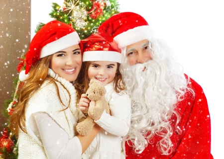 Picture of happy family celebrating New Year eve, little baby girl with parents enjoying winter holidays, father wearing red Santa Claus costume, Christmas magic, happiness and love concept photo