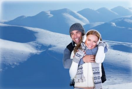 Imagen de la feliz pareja abrazando al aire libre, familia cariñosa joven que se divierte en las montañas cubiertas de nieve, hombre apuesto abrazando a su linda novia, luna de miel en invierno, vacaciones de invierno, el amor concepto Foto de archivo - 16970323