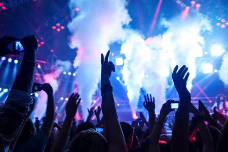 manos aplaudiendo: Foto del concierto de rock, festivales de música, celebración del Año Nuevo víspera, fiesta en la discoteca, pista de baile, discoteca, mucha gente de pie con las manos levantadas y aplaudiendo, la felicidad y el concepto de la vida nocturna