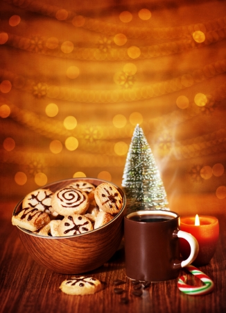Image of Xmas sweets, traditional Christmastime gingerbread with candy cane on festive table, coffee cup decorated with little decorative Christmas tree, tasty homemade cookies, New Year eve photo
