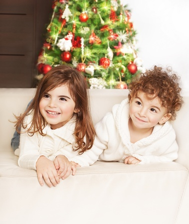 Photo of adorable kids, boy and girl laying down on the sofa and laughing, family at home celebrate Christmas, little babies playing indoor, infant Xmas party, decorated Christmas tree for children photo